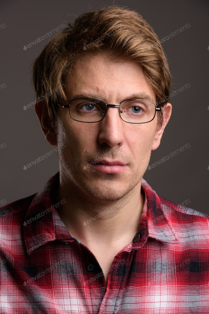 Handsome man wearing eyeglasses against gray background