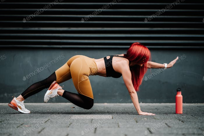 Fit girl doing plank exercise outdoor on a summer day. Concept of fitness and motivation.
