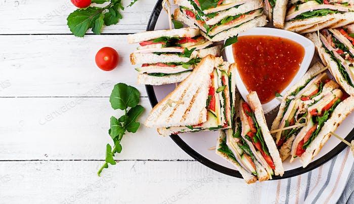 Club sandwich with ham, tomato, cucumber, cheese,  and arugula o