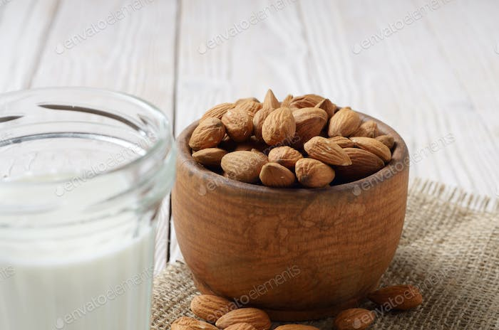 Milk or yogurt in mason jar on white wooden table with bowl of a