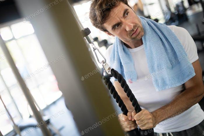 Lifestyle portrait of handsome muscular man after the training in the sport gym