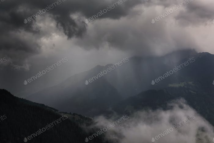 dramatic storm clouds over mountains in summer