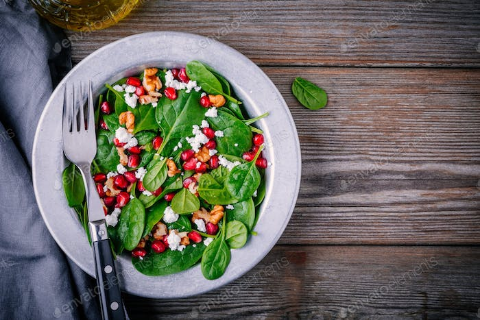 Fresh green salad with spinach, walnuts, goat cheese and pomegranate
