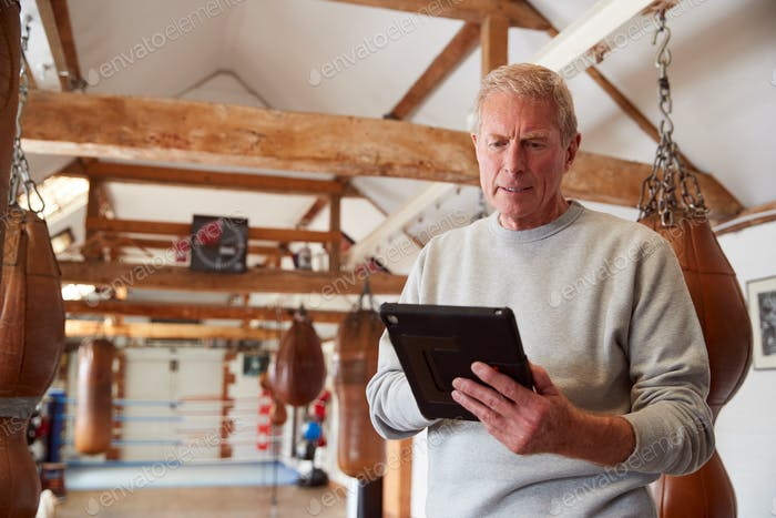Senior Male Boxing Coach In Gym Tracking Training Mit Digital Tablet