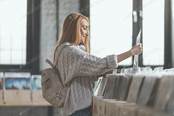 Smiling girl browsing records