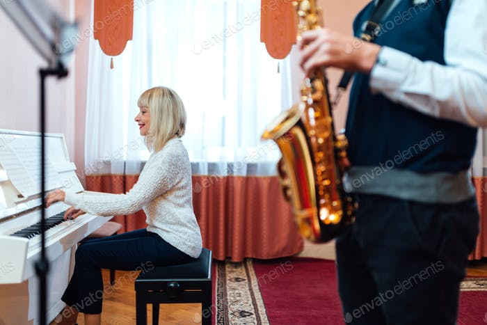 teacher pianist plays the white piano to the accompaniment of saxophone in a music school.
