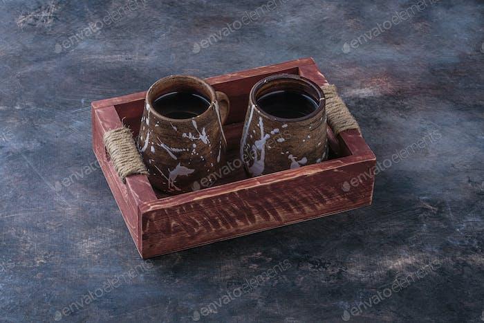 Handmade cups with tea on wooden board, dark photo