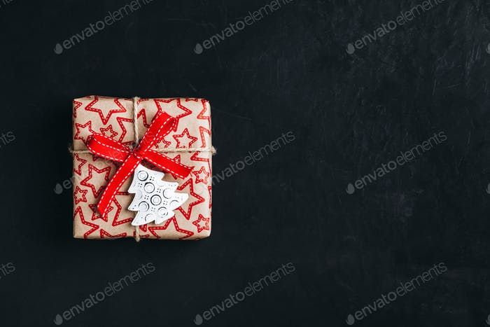 Christmas gift box with red bow ribbon on a dark concrete background.