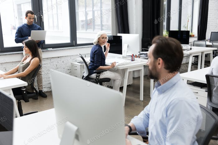 Group of business people talking to each other while working