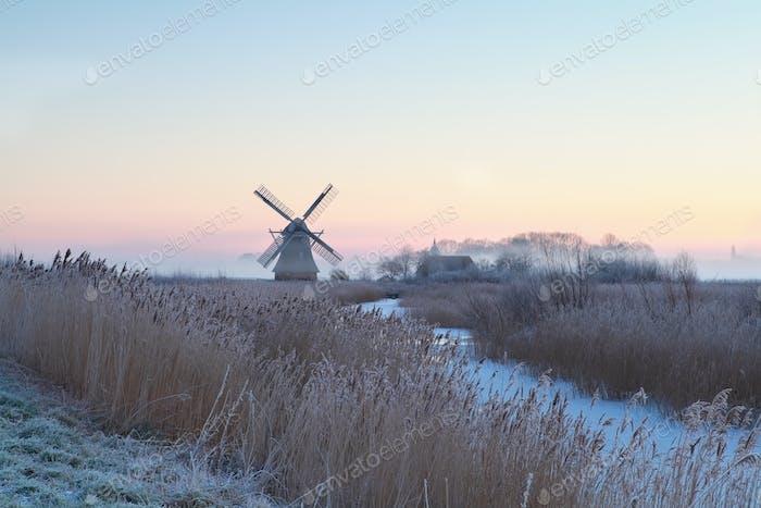 Dutch windmill by river in winter