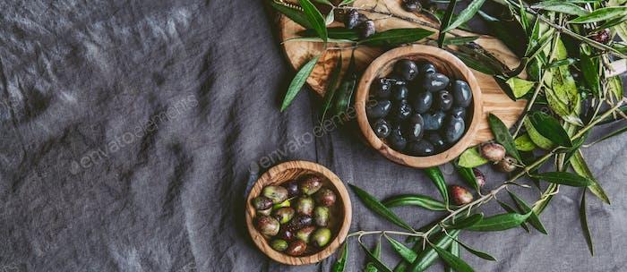 Frische Oliven- und Olivenzweige auf Leinentischdecke.
