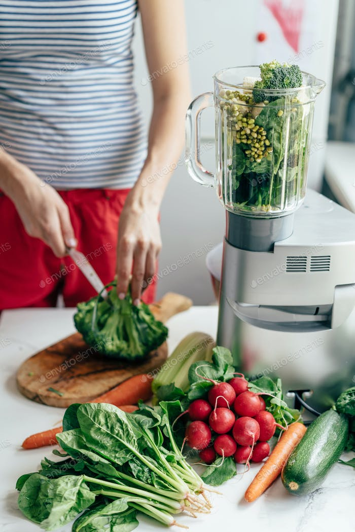 Vertical image. Woman cuts ingredients for a healthy snack. Cook salad and smoothie.