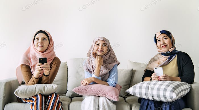 Islamic women friends using smart phone and looking up