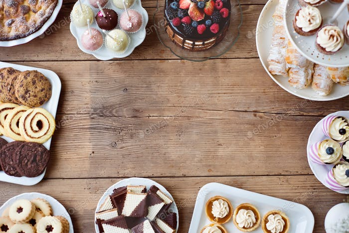 Table with cake, pie, cupcakes, tarts and cakepops. Copy space.