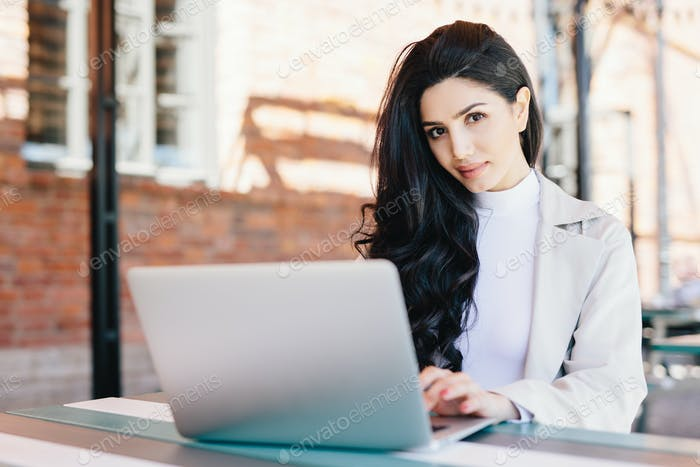 Beautiful female freelancer typing a message via email using laptop while sitting on terrace