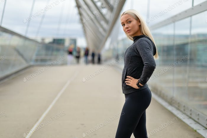 Sporty Woman in Black Workout Outfit Standing At Modern Bridge In City