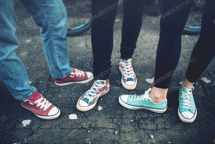 Young rebel teenagers wearing casual sneakers, walking on dirty concrete.