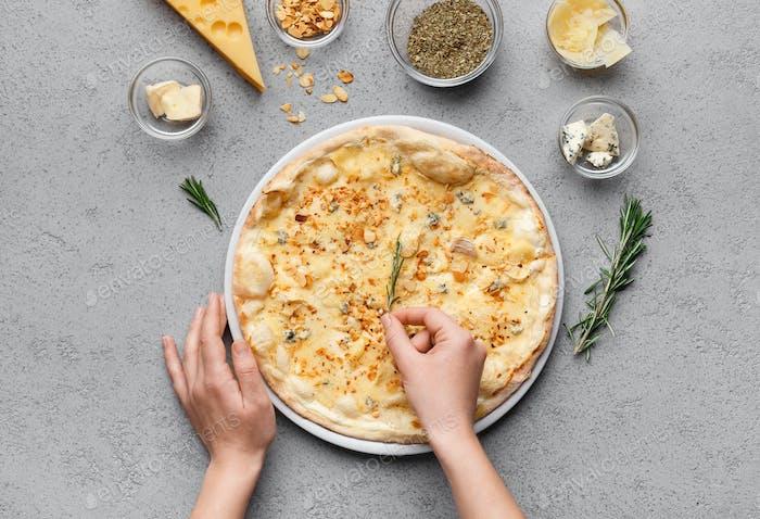 Chefkoch bereitet käsige Pizza vor und schmückt es, Draufsicht