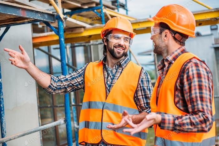 glückliche Baumeister in Warnweste und Schutzhelm, die auf das Bauhaus zeigen
