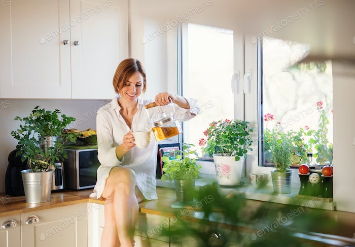 A young woman sitting on worktop indoors in kitchen, pouring tea.
