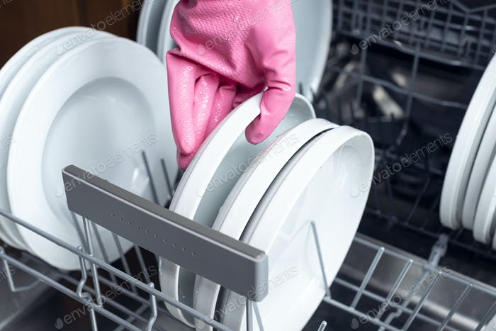Hand putting a plate into dishwasher