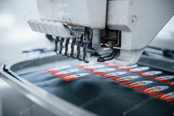 Making rocket pictures. Close up view of white automatic sewing machine at factory in action