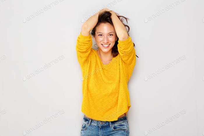 happy asian girl smiling with hands in hair