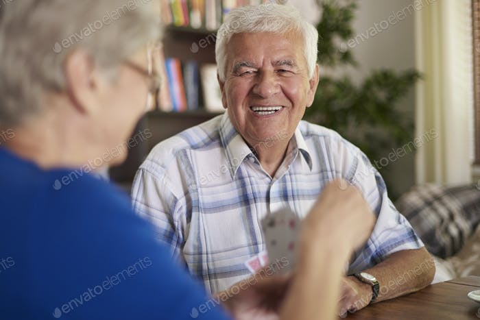 Cheerful grandparents playing cards in the afternoon