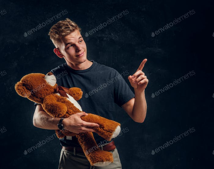 Happy smiling guy is showing something to his plush bear