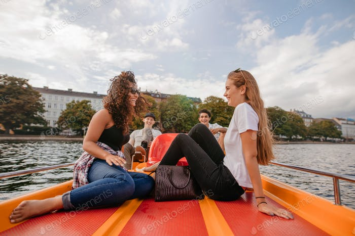 Teenage friends relaxing on pedal boat