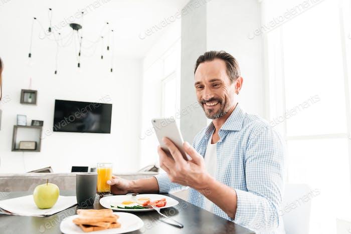 Smiling mature man using mobile phone