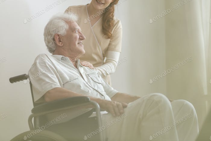 Low angle on smiling and happy disabled elderly man in a wheelch