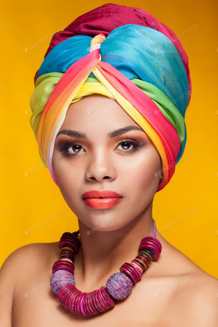 Afro american ethnic girl with turban on yellow background