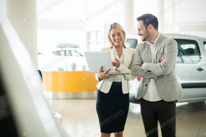 Professional salesperson during work with customer at car dealership.