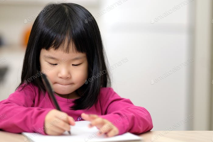 Young little Asian girl learning to write