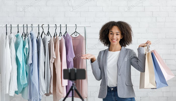 Stylist or personal assistant. Smiling african american woman holding packages and shows on clothes