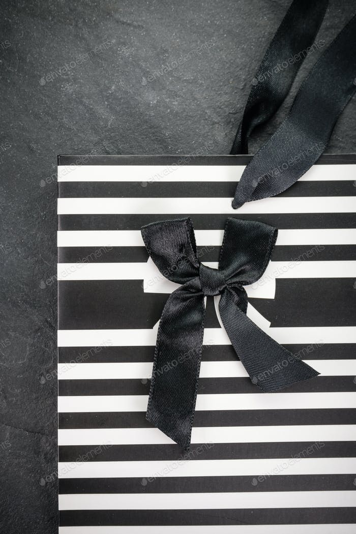 Paper bag in strip with black bow close-up