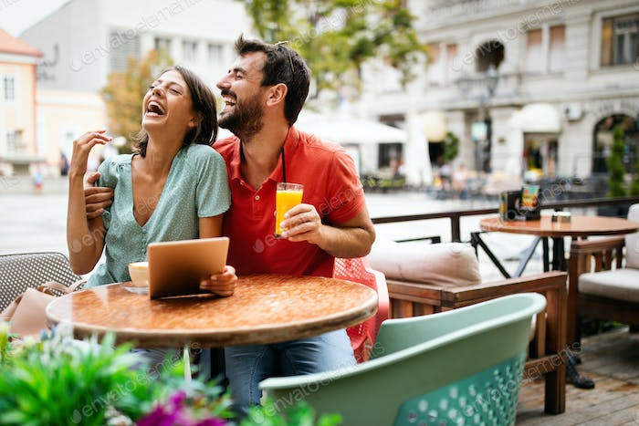 Embracing couple using digital tablet, smiling and talking in cafe