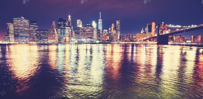 Manhattan skyline reflected in East River at night, NYC.