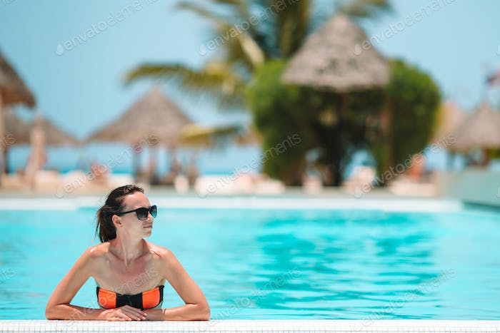 Beautiful woman at luxury resort near pool