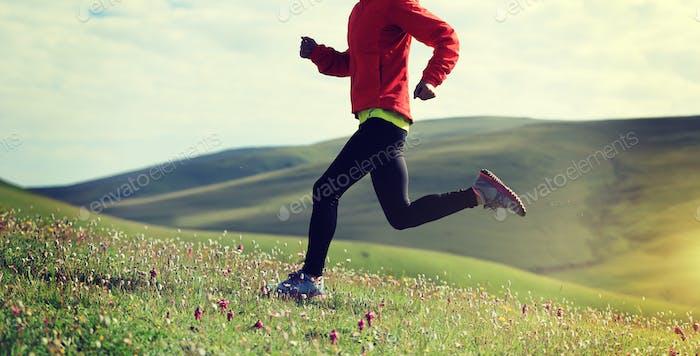 Woman running on grassland mountains