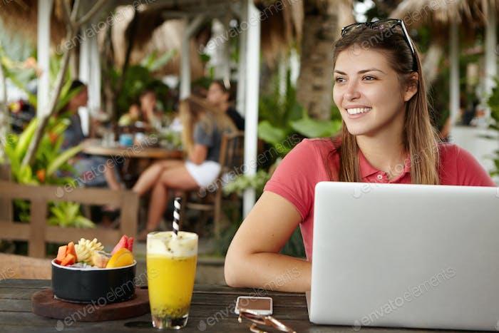 Glückliche junge Selbständige Frau, die eine kostenlose WLAN-Internetverbindung vor dem Gener genießt