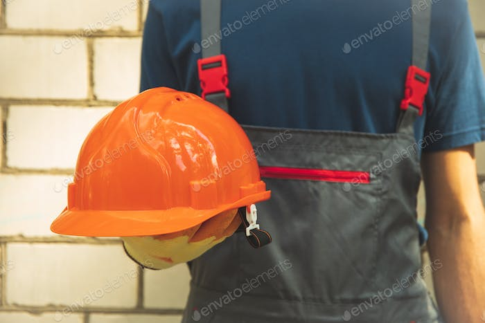 Man in overalls holds safety helmet outdoor
