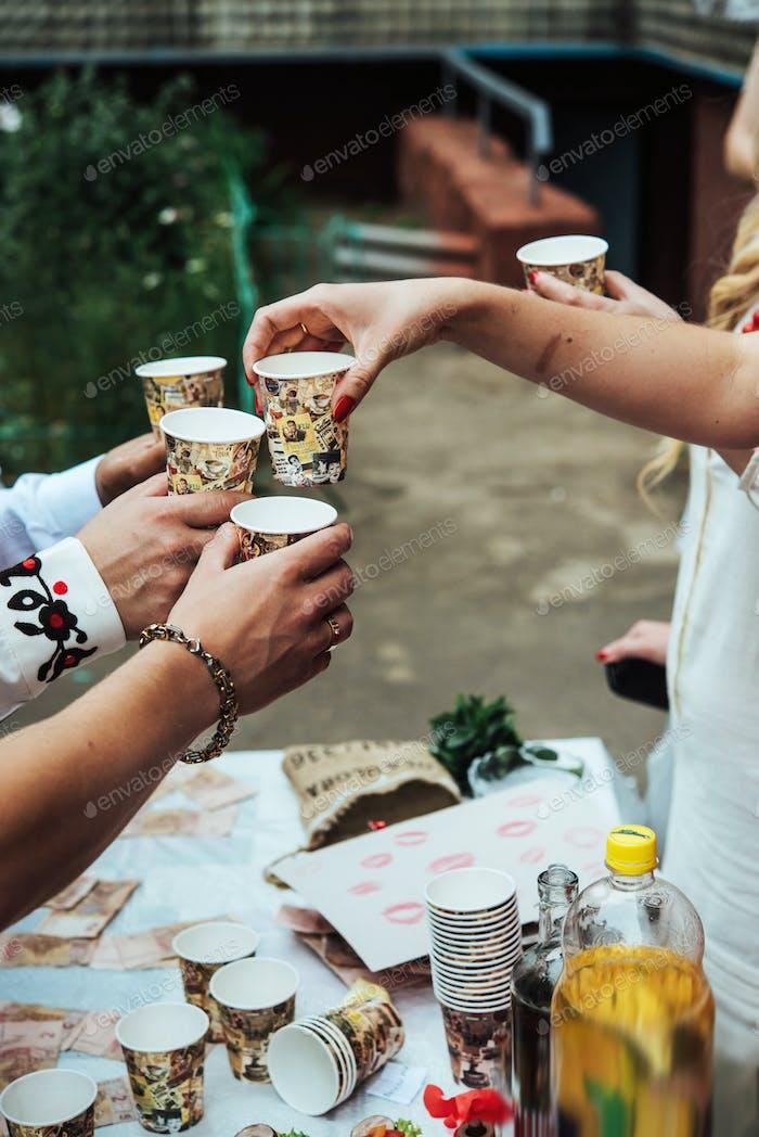 Hände von Menschen mit Tassen Alkohol, Feiern und Toasten, Hochzeit oder Geburtstagsveranstaltung