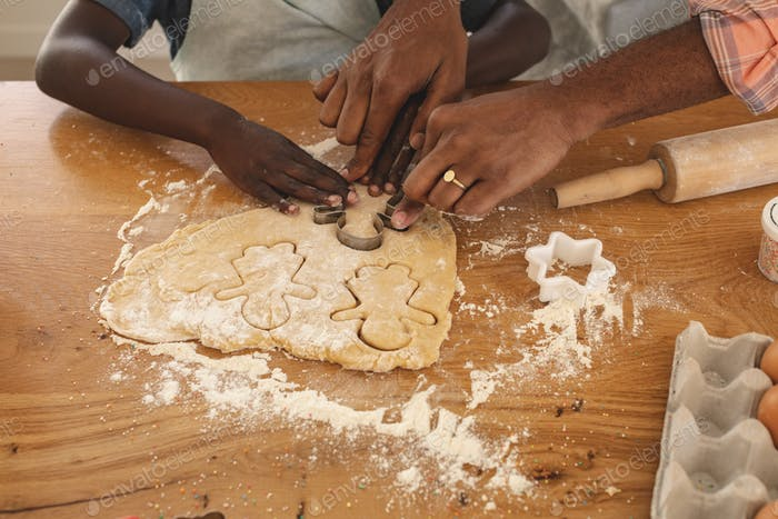 Close-up of African American father and son baking cookies in kitchen at home
