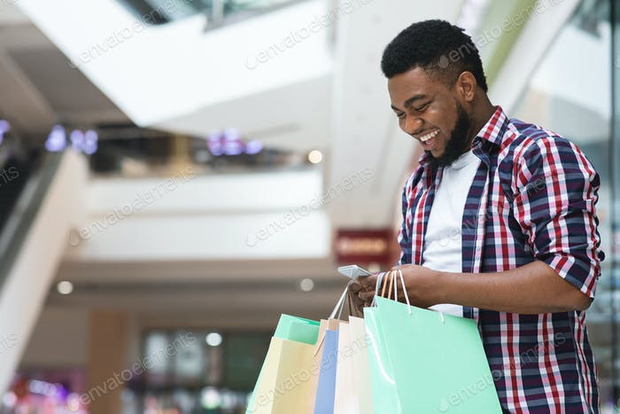 Cashback Bonus. Happy African Man Holding Shopping Bags And Smartphone In Mall