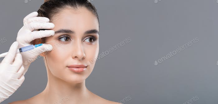 Young woman getting facial beauty injection, panorama