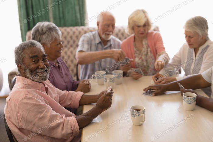 Front view of group of senior people playing cards around table in living room at home