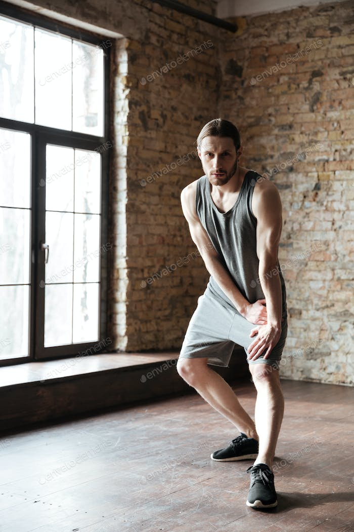 Full length portrait of a concentrated sportsman doing stretching exercises