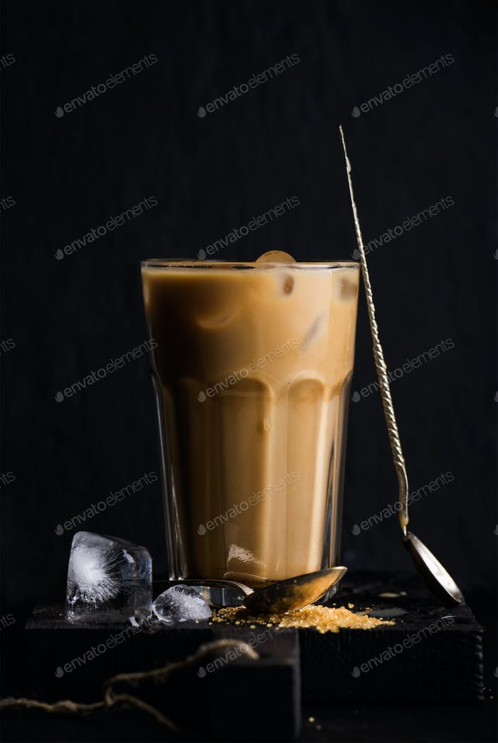 Iced coffee with milk in a tall glass, black background